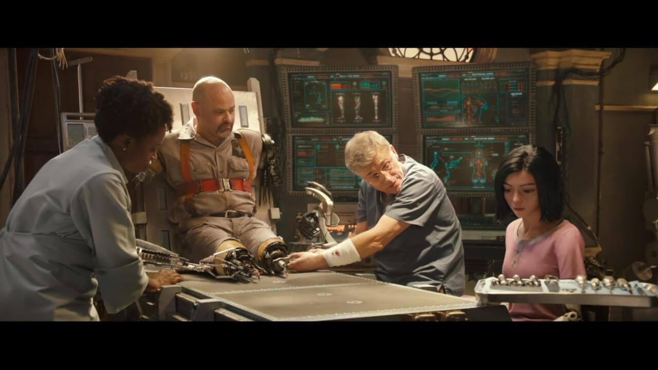 『アリータ: バトル・エンジェル』の主人公・アリータがシドの仕事を手伝っているシーン。アリータを演じるのはローサ・サラザール、シドを演じるのはクリストフ・ヴァルツ。